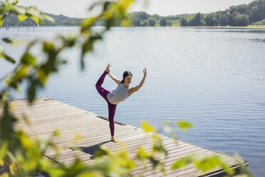 Mature woman practicing yoga in summer on a jetty at a lake - MOEF01763