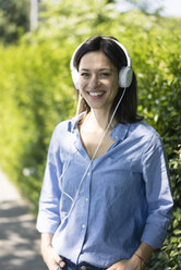 Woman with headphones listening music in nature - MOEF01769