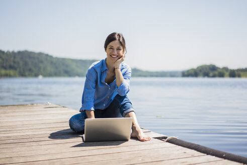 Mature woman working at a lake, using laptop on a jetty - MOEF01778