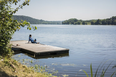 Mature woman sitting on a jetty at a lake, taking a break - MOEF01781