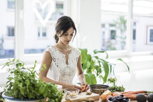 Woman preparing healthy food in her kitchen - MOEF01787