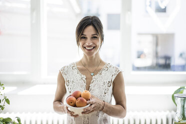 Woman holding bol of apricots in her kitchen - MOEF01790