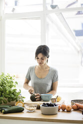 Woman preparing healthy food in her kitchen - MOEF01796