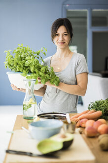 Woman standing in kitchen, holding pot of basil - MOEF01799