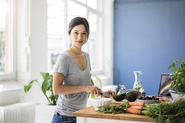Woman preparing healthy food in her kitchen - MOEF01805