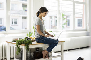 Woman sitting on kitchen table, searching for healthy recipes, using laptop - MOEF01808