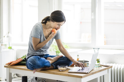 Woman sitting on kitchen table, searching for healthy recipes, using laptop - MOEF01814