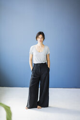 Womans standing barefoot with hands in pocket in front of blue background - MOEF01817