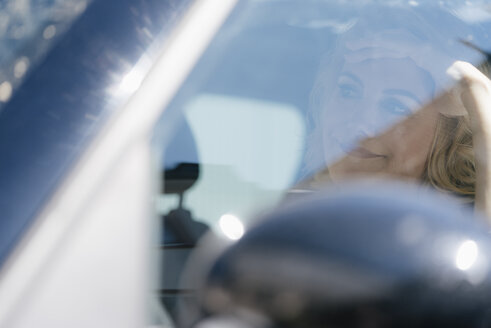 Annoyed blond woman in car - KNSF05395