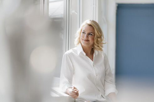 Confident blond woman wearing white shirt looking out of window - KNSF05404