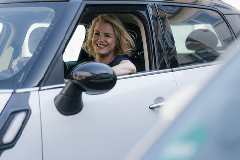 Portrait of smiling woman looking out of car window - KNSF05416