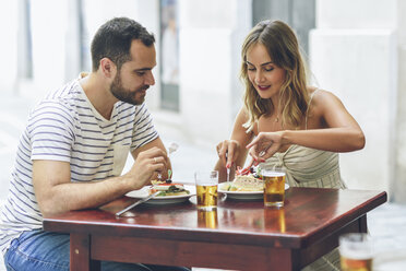 Couple eating and drinking beer in a restaurant on the street - JSMF00596