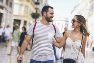 Spain, Andalusia, Malaga, happy tourist couple walking in the city - JSMF00599