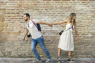 Couple holding hands walking in opposite directions at brick wall - JSMF00602
