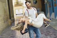 Spain, Andalusia, Malaga, man carrying girlfriend in the city - JSMF00605