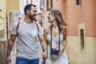 Spain, Andalusia, Malaga, happy tourist couple walking in the city - JSMF00614