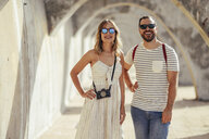 Spain, Andalusia, Malaga, happy tourist couple standing under an archway in the city - JSMF00617