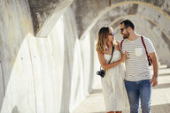 Spain, Andalusia, Malaga, happy tourist couple walking under an archway in the city - JSMF00620