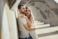 Spain, Andalusia, Malaga, affectionate tourist couple hugging under an archway in the city - JSMF00626