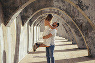 Spain, Andalusia, Malaga, happy man lifting up girlfriend under an archway in the city - JSMF00629