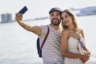 Spain, Andalusia, Malaga, happy tourist couple taking selfie with smartphone at the coast - JSMF00638