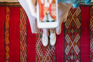 Low section of woman photographing with smart phone while standing on traditional rug - CAVF57803