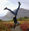 Excited female hiker doing handstand on field against mountains - CAVF57926