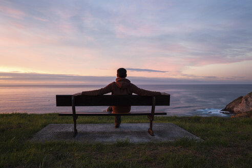 Full length of man looking at sea while sitting on bench against cloudy sky during sunset - CAVF57929