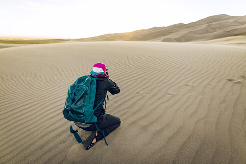 Full length of hiker with backpack photographing while kneeling at Great Sand Dunes National Park - CAVF57947