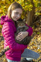 Portrait of smiling girl holding tabby cat outdoors in autumn - SARF03996