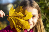 Portrait of smiling girl looking through hole in autumn leaf - SARF03999