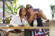 Happy girlfriends sitting outdoors with cocktail glasses taking a selfie - ERRF00234