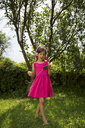 Singing girl with headphones and smartphone dancing in the garden - LVF07575