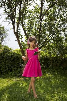 Singing girl with headphones and smartphone dancing in the garden - LVF07575