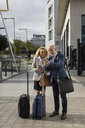Senior businessman and businesswoman with baggage using cell phones in the city - MAUF01775