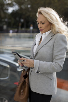 Senior businesswoman checking cell phone in the city - MAUF01781