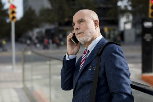 Senior businessman talking on cell phone in the city - MAUF01784