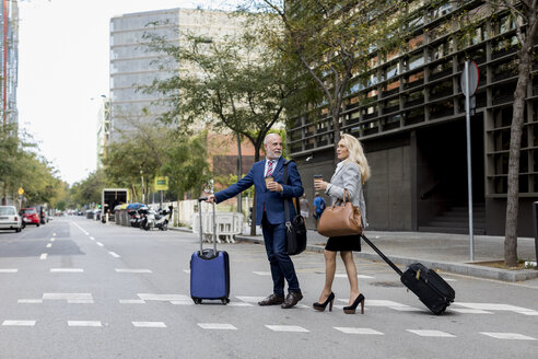 Senior businessman and businesswoman with baggage crossing the street in the city - MAUF01805