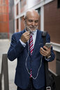 Senior businessman with cell phone and earphones outdoors - MAUF01814