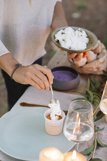 Close-up of woman preparing a romantic candlelight meal outdoors - ALBF00707