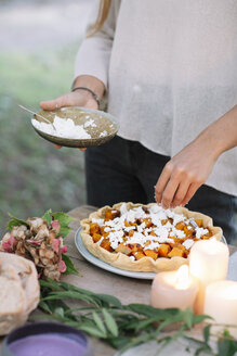 Close-up of woman preparing a romantic candlelight meal outdoors - ALBF00710