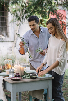 Couple preparing a romantic candlelight meal outdoors - ALBF00713