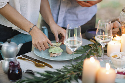Close-up of couple preparing a romantic candlelight meal outdoors - ALBF00716