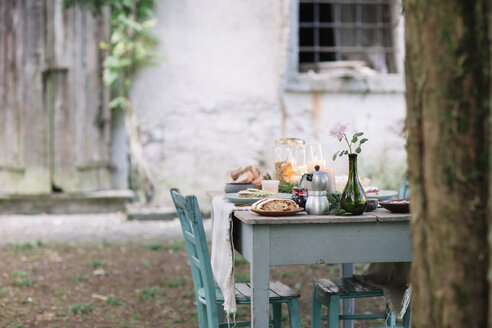 Laid garden table with candles next to a cottage - ALBF00719