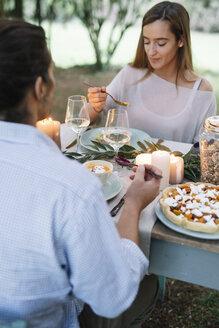 Couple having a romantic candlelight meal in garden - ALBF00728