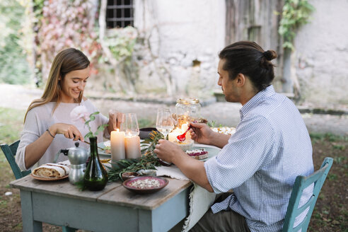 Couple having a romantic candlelight meal next to a cottage - ALBF00731