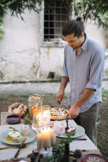 Man arranging a romantic candlelight meal outdoors - ALBF00734