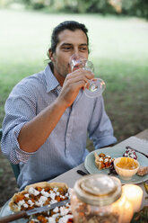 Man drinking glass of wine at garden table - ALBF00737