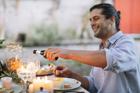 Man pouring out sparkling wine at garden table - ALBF00740