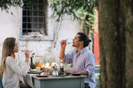 Couple having a romantic candelight meal drinking from wine glasses - ALBF00743